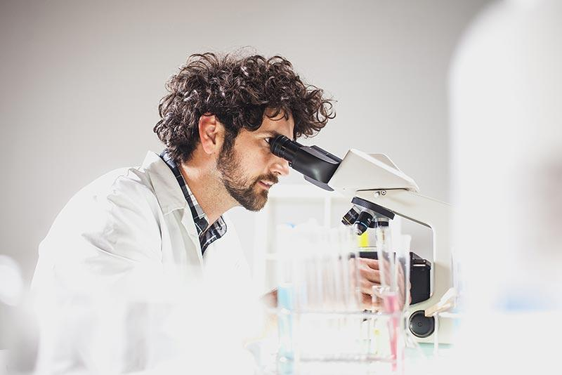Biotech scientist looking through microscope